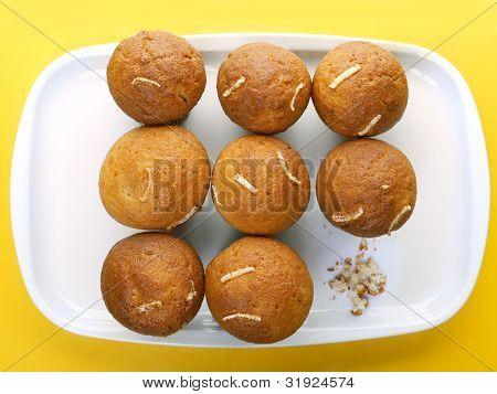 Nueve cupcakes en placa y migas de uno que ha sido comido - tiro desde arriba