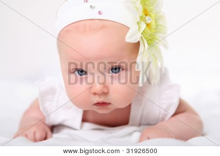 Portrait of a baby girl with a flower on her head on a white background