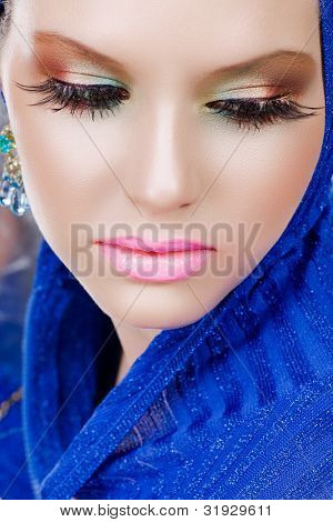 portrait of a beautiful woman with long false feather eyelashes and bright make-up wearing blue