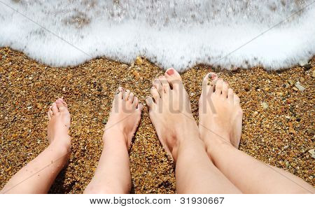 feet of child and mom in the sea waves