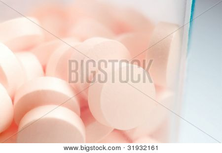 Pink pills over white macro shot