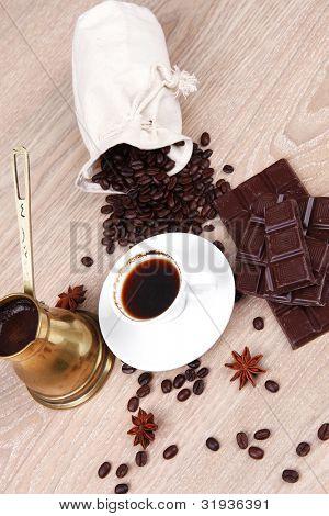 Süßes heisses Getränk: schwarzer Kaffee mit Bohnen in eine weiße Tasche auf einem Holztisch mit Streifen von dunklen Choc