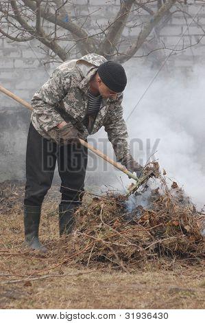 Man burn out dry grass in the garden.Ukraine
