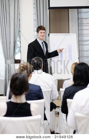 young  male business man giving a presentation at a  meeting seminar at modern conference room  on a table board