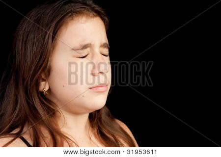 Dramatic portrait of a girl with a very sad face crying isolated on black with space for text