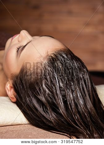poster of young  woman receiving hair care procedure  in spa salon. Beauty treatment. Spa salon