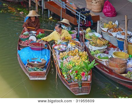 RATCHABURI, THAILAND - FEB 20: A woman buying chili for Thai food at Damnoen Saduak floating market on February 20, 2011 in Ratchaburi, Thailand. The  market is popular for traditional style food.