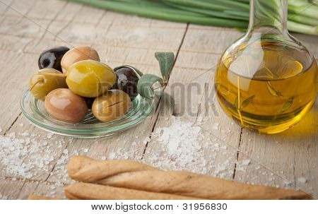 Olive oil bottle, olives and pretzels on wooden table