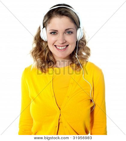 Smiling Young Woman Listening Music In Headphones