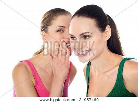 Young Beautiful Girl Whispering Secret In Her Friends Ear