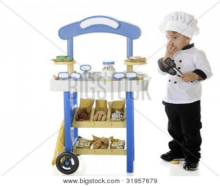 "A preschool ""baker-chef"" snitching cookies from his vending stand.  Signs on the stand are left blank for your text.  On a white background."