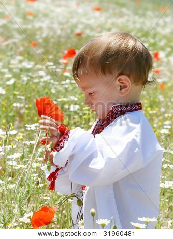 young boy in traditional clothes in flower field