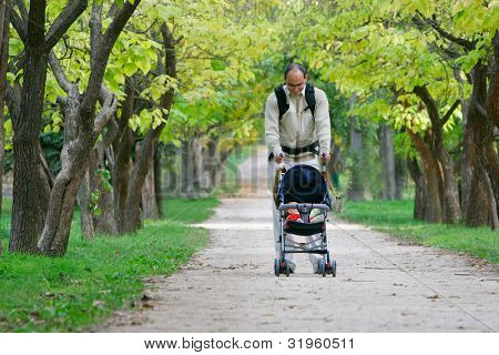 father and baby in stroller walking in park