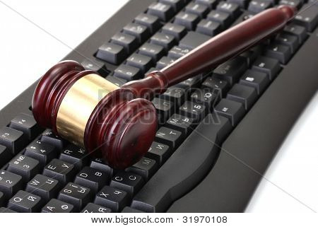 wooden gavel on keyboard isolated on white