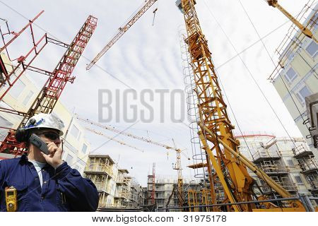 construction engineer talking in phone, large building-site in background, cranes and scaffoldings, wide perspective