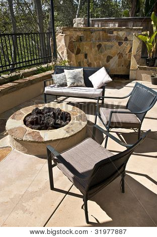 Custom Home backyard - chairs, fire-pit, and Italian style stone waterfall
