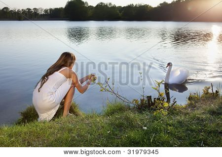 blond woman on water background and swan
