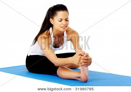 Hispanic woman feeling pain while doing the head to knee yoga pose. This is part of a series of various yoga poses by this model, isolated on white