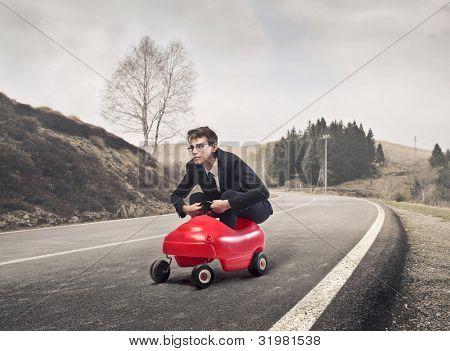 Junge Unternehmer ein Spielzeugauto auf einer Landstraße fahren