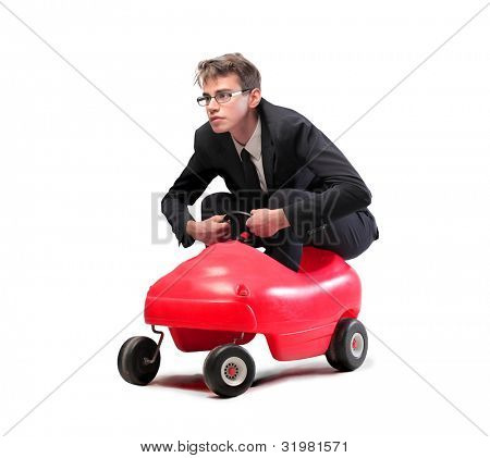 Young businessman driving a toy car