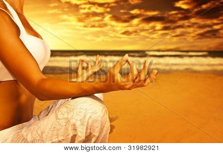 Yoga meditation on the beach, healthy female body in peace, woman sitting relaxed on sand over beautiful sea sunset, calm girl enjoying nature, active vacation lifestyle, zen spa, wellness concept