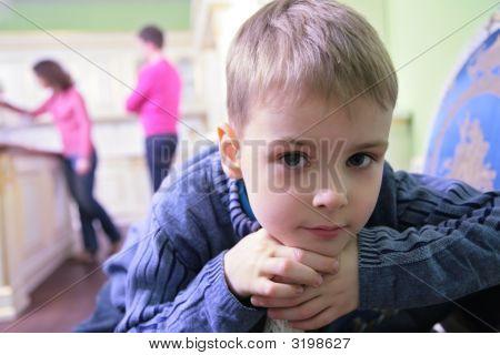 Portrait Of Pensive Boy On Kitchen Against Background Of Parents
