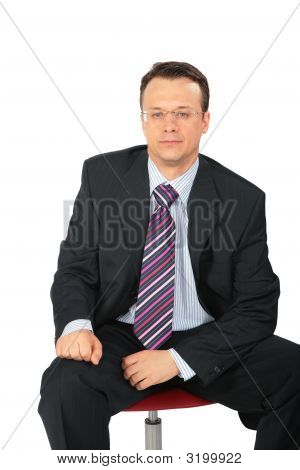 Businessman In Glasses Sits On Chair