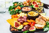 Meat And Cheese Appetizer Platter. Sausage, Cheese, Hummus, Vegetables, Fruits And Bread On A Black  poster