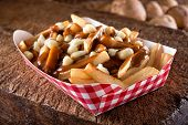 A Serving Of Delicious Poutine With French Fries, Cheese Curds And Gravy On A Rustic Wooden Board. poster