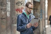 image of serbia  - Young man with yellow glasses use iPad tablet computer on street - JPG