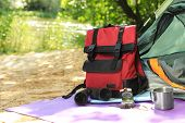 Camping Equipment And Modern Tent In Wilderness. Space For Text poster
