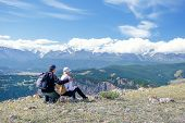Couple Travelers Man And Woman Sitting On Cliff Relaxing Mountains And Enjoying Valley View.  Happy  poster