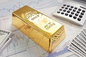 Gold ingot resting on a stocks and shares graph representing investment or banking poster