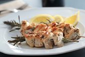 stock photo of souvlaki  - Chicken souvlaki on rosemary sticks with lemon - JPG