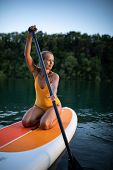 SUP Stand up paddle board concept - Pretty, young woman paddle boarding on a lovely lake in warm lat poster