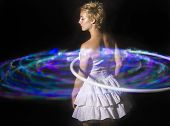 stock photo of hula hoop  - Young woman in white dress hula-hooping against a black background with LED hoop.