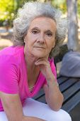 Serious Old Lady Relaxing In Park. Senior Grey Haired Woman In Casual Sitting On Bench Outdoors And  poster