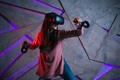 Use A Sword. A Young Woman In A Virtual Helmet Uses Controllers In Both Hands, Like The Arms Of Virt poster