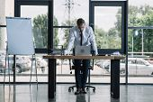 Upset Businessman Standing Near Desk And Laptop In Office poster