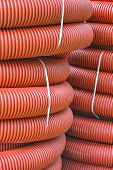 Coils Of New Red Plastic Pipe With Rain Drops. Red Plastic Tubing For Underground Cable Protection.  poster