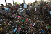 BALI, INDONESIA - APRIL 11: Poor people from Java island working in a scavenging at the dump on Apri