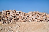 Brown Granite. Big Pile Of Rocks For Construction And Boulders Piled In A Heap Under A Blue Sky In S poster