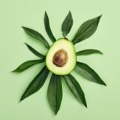 Slices of avocado on color background. Whole and half with Leaves. Simple and minimal food Top View. poster