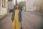 Young Beautiful Fashion Woman Wearing Stylish Yellow Jumpsuit Posing On European City Streets. poster