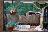 Beautiful Scenery Of The Rustic Veranda: Pots With Purple Flowers, A Lamp, Decoration With Various F poster