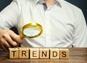Wooden Blocks With The Word Trends And Businessman With A Magnifying Glass. Popular And Relevant Top poster