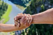 The Male Hand Embraces The Female Hand Against The Backdrop Of The Natural Landscape. A Helping Hand poster