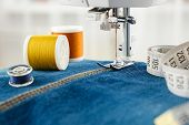 Sewing Denim Jeans With Sewing Machine. Close Up Of Needle Of Sewing Machine On The Denim Fabric Sti poster