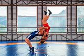 The Concept Of Fair Wrestling. Two Greco-roman  Wrestlers In Sportwears Makes A Throw Through The Ch poster