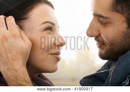 Closeup photo of romantic kissing couple, side view.
